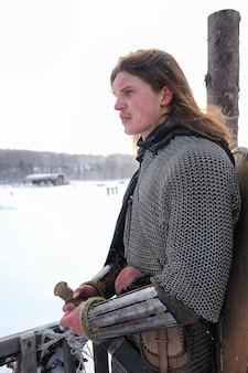 Broń młodego wojownika w kolczudze uzbrojonego w miecz i topór