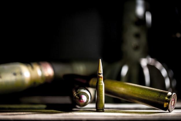 Broń, nabój na drewnianym tle