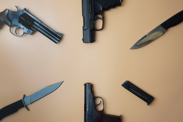 Broń palna rozłożona na okręgu. trzy pistolety pistolety, naboje, noże wojskowe z bliska na neutralnym beżowym tle.