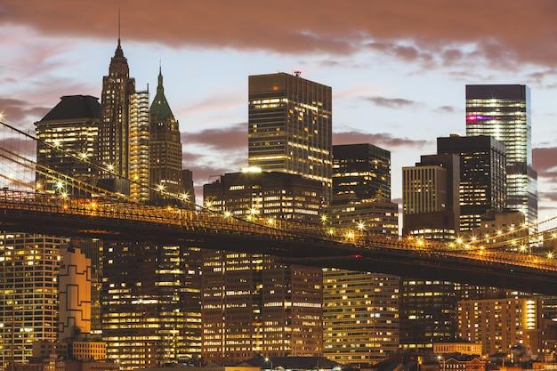 Brooklyn bridge i downtown skyscrapers w nowym jorku o zmierzchu