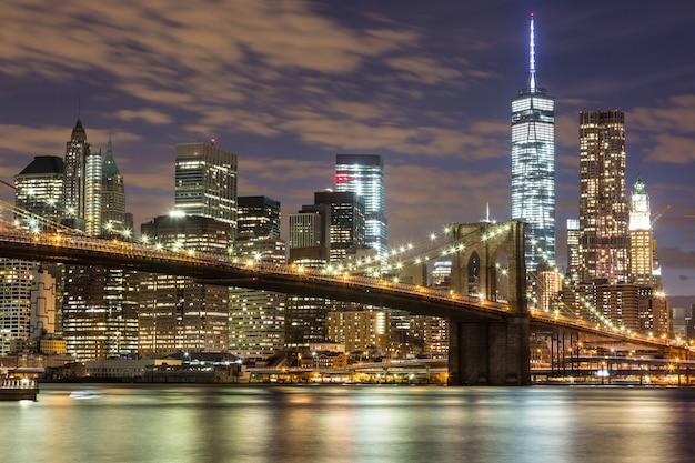 Brooklyn bridge i downtown skyscrapers w nowym jorku w nocy