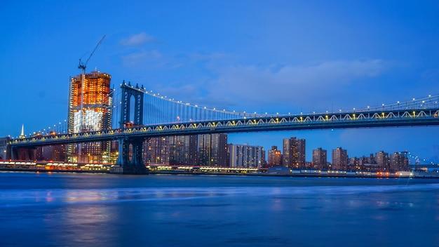 Brooklyn bridge i nyc skylinet noc z odbiciem panoramy east river