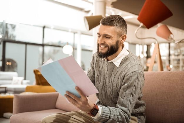 Broszura sklepu meblowego. śmiejący się brodacz, który szuka potrzebnych mebli, przeglądając papiery w rękach