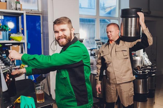 Browar rozlewa piwo do szklanych butelek na liniach przenośników. prace przemysłowe, zautomatyzowana produkcja żywności i napojów. prace technologiczne w fabryce.