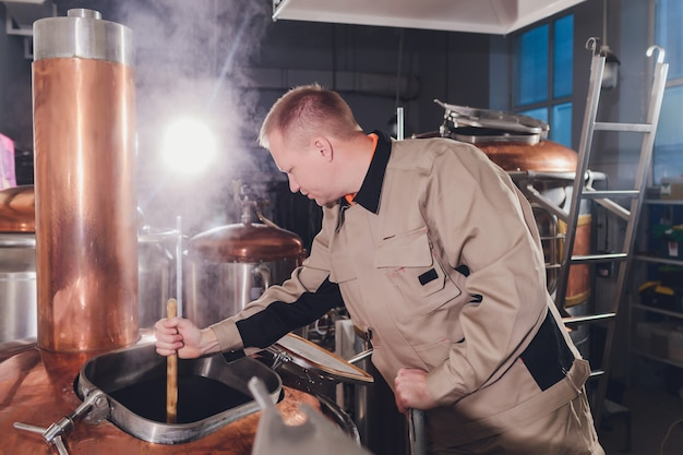 Browar w warzelni wylewając słód do zbiornika.