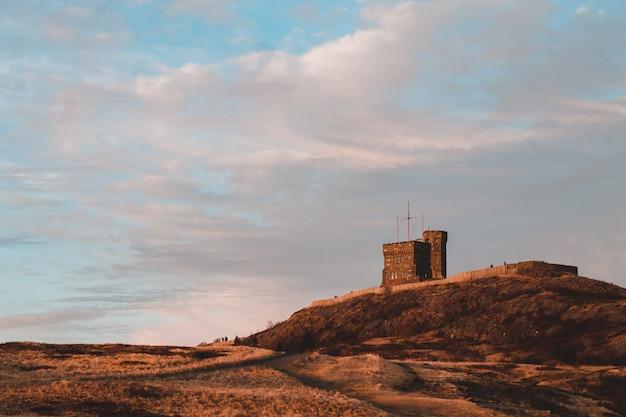 Brown betonowy budynek na brown wzgórzu pod białymi chmurami podczas dnia