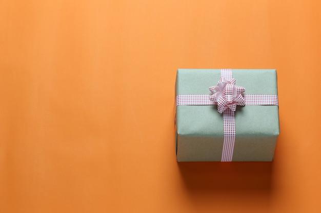 Brown christmas gift box umieszczone na pomarańczowym papierze sztuki podłogi i kopia przestrzeń.