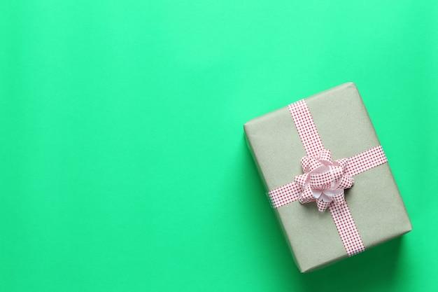 Brown christmas gift box umieszczone na zielonej podłodze papieru sztuki i kopia przestrzeń.