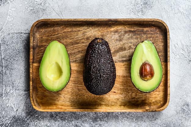 Brown dojrzałe avocado połówki na drewnianej ciapanie desce. szare tło. widok z góry