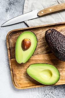 Brown dojrzałe avocado połówki na drewnianej ciapanie desce.