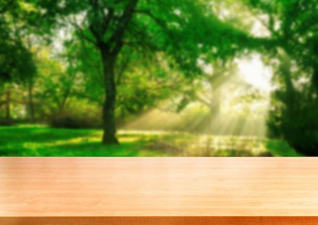 Brown drewna stół w zielonym plamy natury tle.