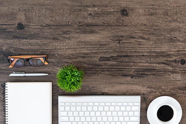 Brown drewniany biurowy stół i wyposażenie dla pracować i słuchać muzykę z białym hełmofonem w odgórnym widoku i kopii przestrzeni.