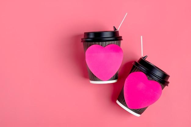 Brown filiżanki, czerwony sercowaty majcher na różowym tle. happy valentine's day flat lay