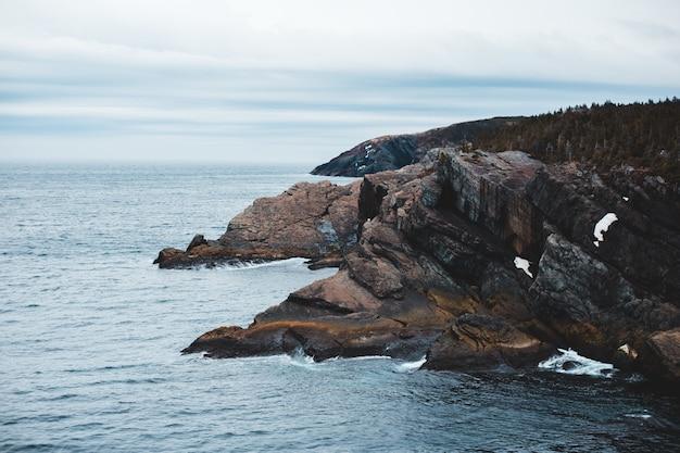 Brown formacja skalna na morzu pod białymi chmurami w ciągu dnia
