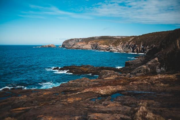 Brown i zielona góra obok błękitnego morza pod niebieskim niebem podczas dnia