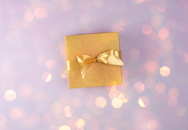 Brown papierowy pudełko z łękiem na purpurowym tle z błyszczącym żółtym bokeh