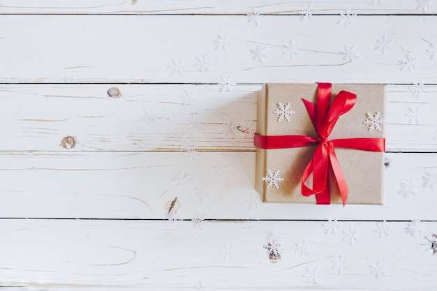 Brown prezenta pudełko i bożenarodzeniowe teraźniejszość na białym drewnianym stołowym tle.