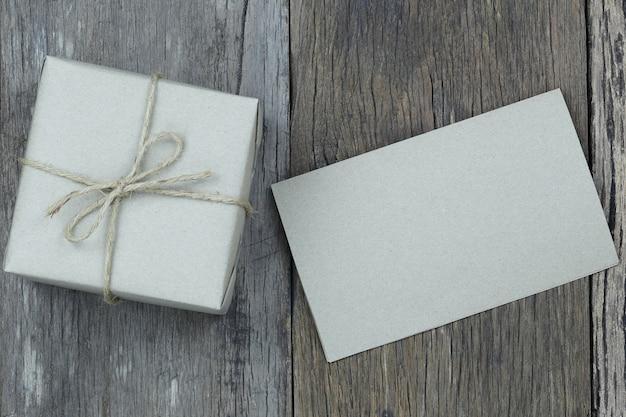 Brown prezenta pudełko i pusty papier na drewnianej podłoga i kopii przestrzeń.
