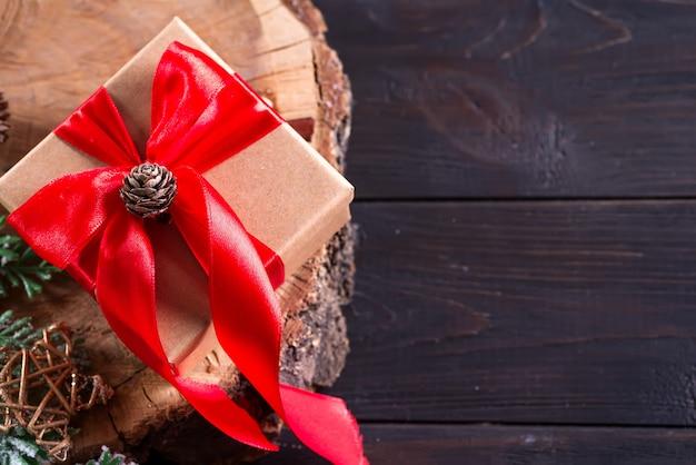 Brown prezenta pudełko z czerwonym łękiem, boże narodzenie dekoracja na drewnianej tnącej desce na ciemnym drewnianym, odgórnym widoku