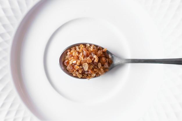 Brown rockowy cukier w łyżce umieszczającej na bielu talerzu. widok z góry