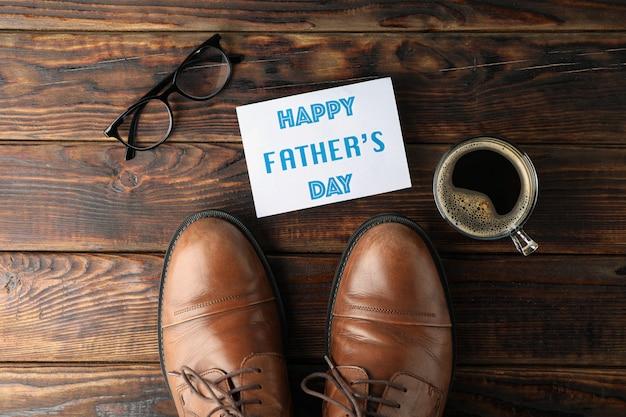 Brown rzemienni buty, wpisowy szczęśliwy ojca dzień, filiżanka kawy i szkła na drewnianym tle, przestrzeń dla teksta i odgórny widok