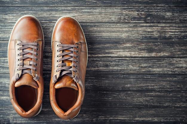 Brown rzemienni mężczyzna buty na drewnianym odgórnym widoku z kopii przestrzenią