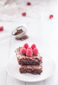Brownie czekoladowe ułożone z malinami.