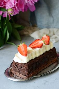 Brownie czekoladowe z przewiewną śmietaną waniliową i świeżymi truskawkami. ciasto czekoladowe ze śmietaną i świeżymi jagodami. deser herbaciany