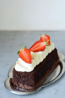 Brownie czekoladowe z przewiewną śmietaną waniliową i świeżymi truskawkami