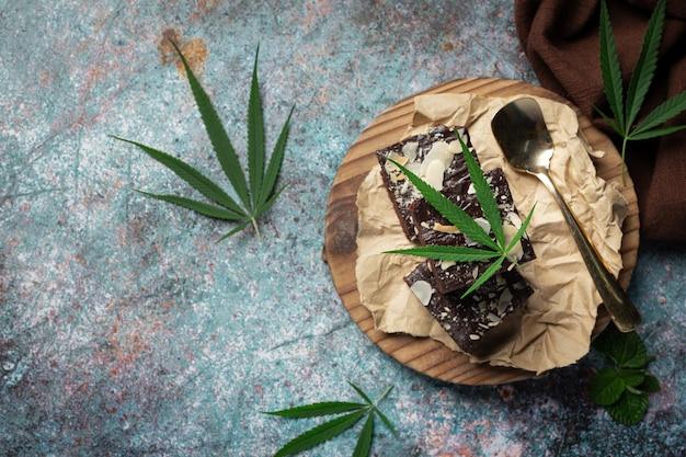Brownie i liście konopi indyjskich ułożone na drewnianej desce do krojenia