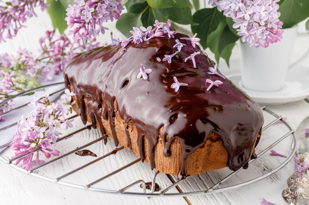 Brownie, podlane czekoladą na drewnianym stole z bukietem bzu
