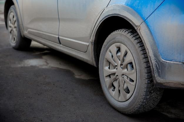 Brud i kurz na karoserii i kołach samochodu, chemikalia i sól powodują korozję metalu