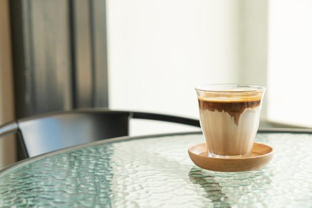 Brudna kawa - szklanka espresso zmieszana z zimnym świeżym mlekiem w kawiarni i restauracji
