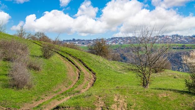 Brudna kręta droga na zielonym wzgórzu