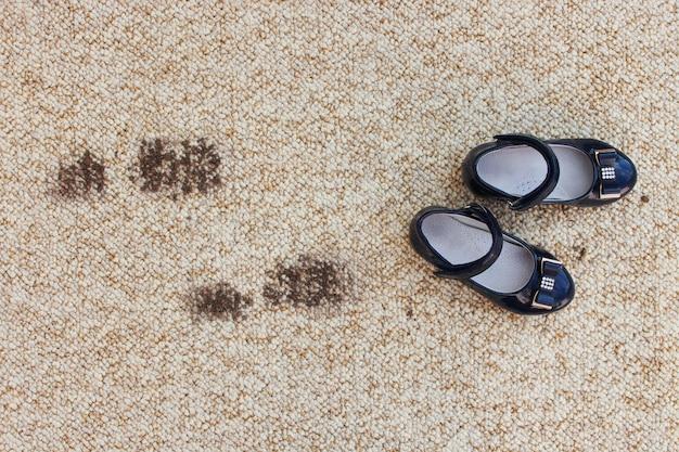 Brudna podłoga i obuwie dziecięce. pojęcie dziecka zabrudzonego dywanu.