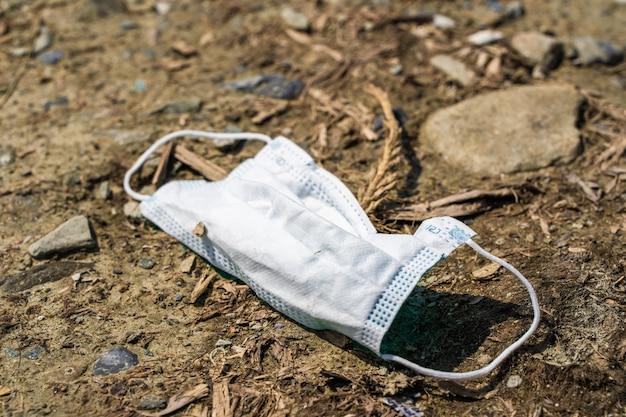 Brudna używana maska medyczna leżąca na ziemi. koronawirus, koncepcja covid-19.