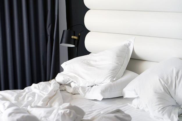 Brudne łóżko w hotelu. pokój koc poduszki brudne łóżko.