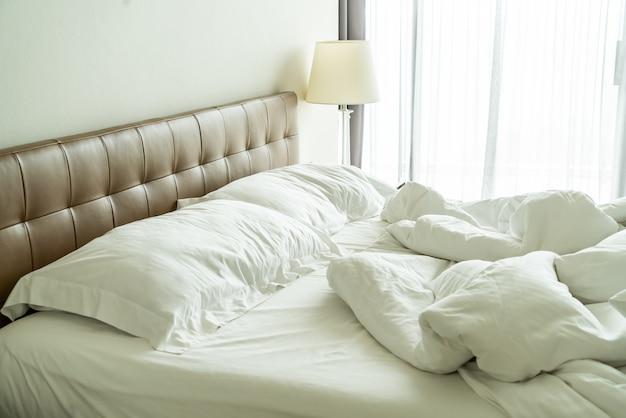 Brudne łóżko z białą poduszką i kocem na łóżku