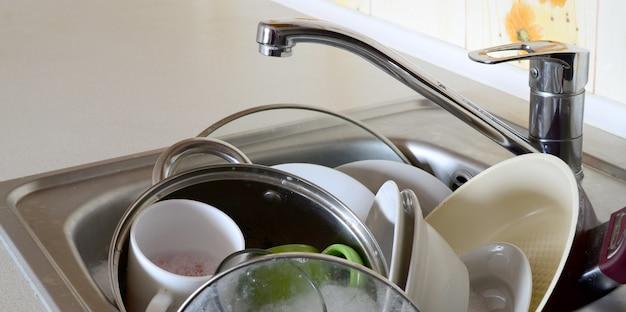 Brudne naczynia i niedomyte urządzenia kuchenne wypełniały zlew kuchenny
