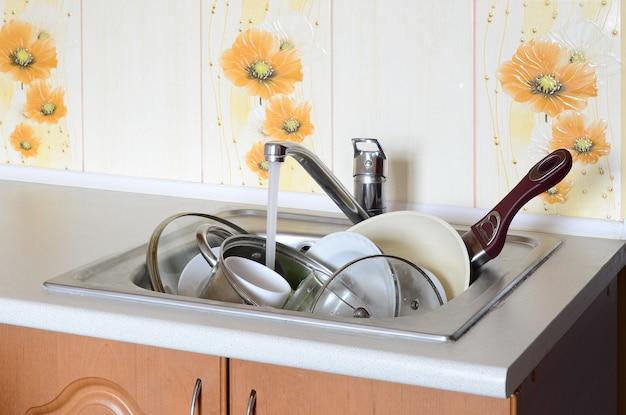 Brudne naczynia i nieumyte sprzęty kuchenne leżą w piankowej wodzie pod kranem z kranu kuchennego
