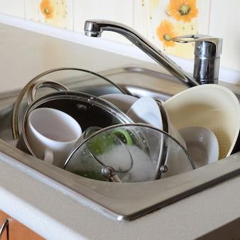 Brudne naczynia i nieumyte sprzęty kuchenne wypełniały zlew kuchenny