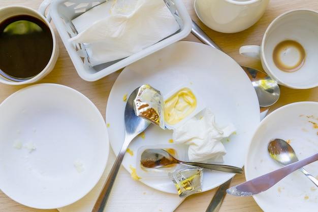 Brudne naczynia na stole. odpady z gospodarstw domowych są szkodliwe dla środowiska.