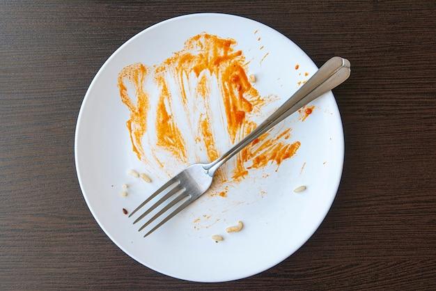 Brudne naczynie z resztkami jedzenia z czerwonym sosem. biały talerz i widelec na stole.