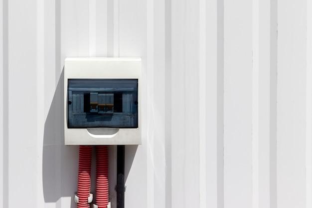 Brudne pudełko z wyłącznikami i kanałem kablowym wychodzącym z niego na białej metalowej ścianie