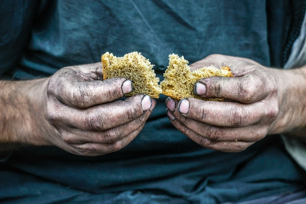 Brudne ręce bezdomnego biedaka z kawałkiem chleba w nowoczesnym społeczeństwie kapitalizmu