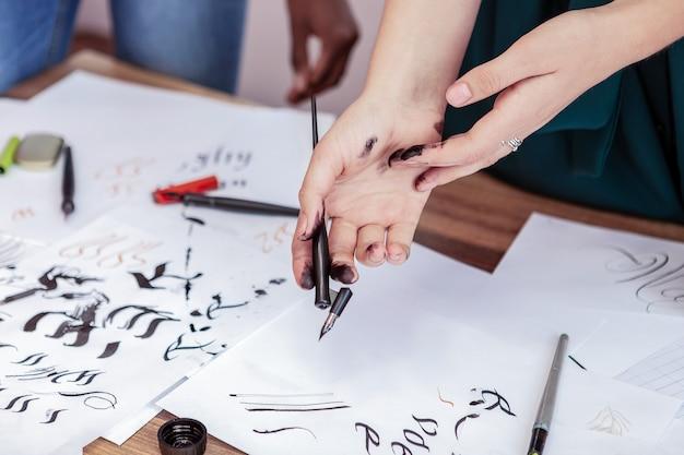 Brudne ręce. młody obiecujący profesjonalny artysta o brudnych rękach podczas ćwiczenia rysunku piórem