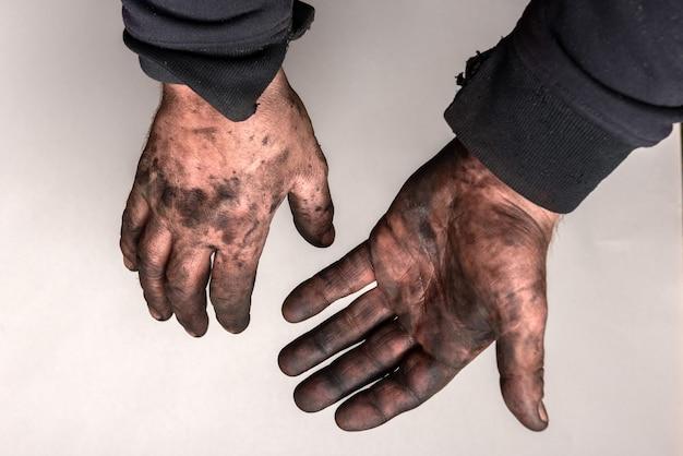 Brudne ręce w masucie samochodu (czarny olej) na szarej ścianie.