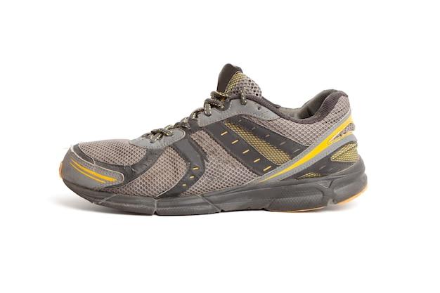 Brudne stare buty do biegania z dziurą na białym tle