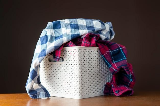 Brudne ubrania w plastikowym koszu w pralni leżały na pralce i stole b