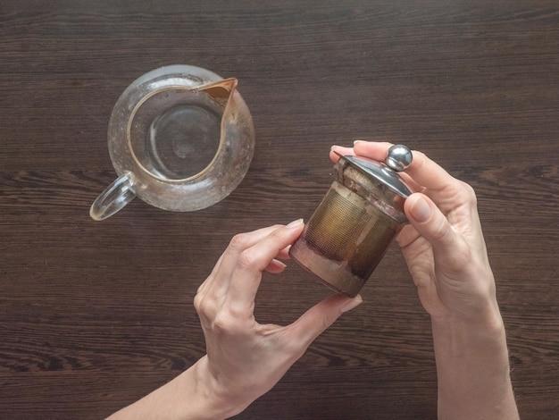 Brudny czajnik trzymając się za ręce